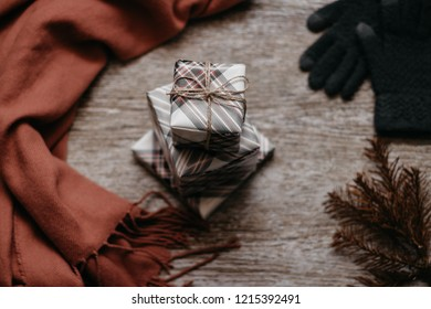 Christmas concept. Presents, scarf  spruce brunches and gloves on the wooden table. Top view image