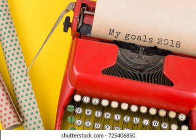 "Christmas concept - red typewriter with the text ""My goals 2018"" and wrapping papaer on yellow background"