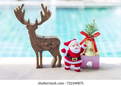Christmas concept, santa claus with wooden reindeer with golden bell over blurred blue background