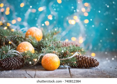 christmas concept with Tangerines, Fir , lights ,Snow, boke and snowflakes, on wooden background
