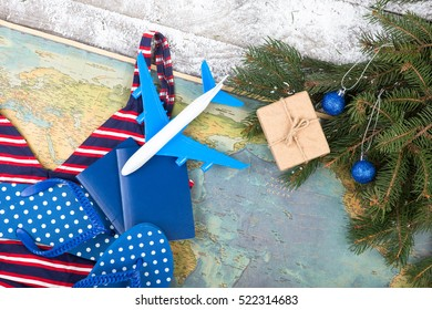 Christmas concept - travel. Fir branches with snow, maps, swimsuit, passports, gift box, flops and toy airplane