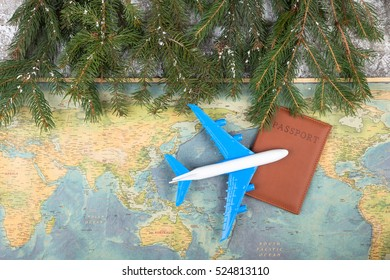 Christmas concept - travel. Fir branches with snow, maps, passport and toy airplane