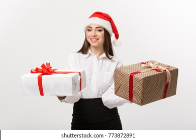 Christmas Concept - young happy caucasian business woman with santa hat giving a choice of gift boxs to camera with copy space on side.