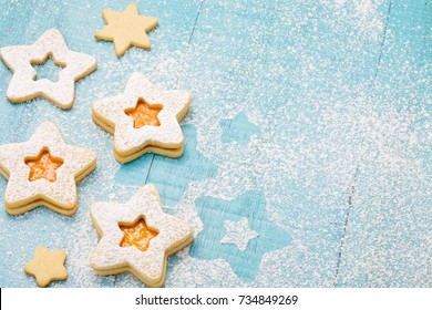 Christmas cookies with apricot jam and icing sugar on a blue background.