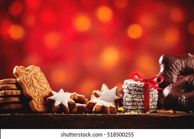 Christmas cookies and biscuits festive background arranged on a rustic wooden table with spicy speculoos, starsand chocolate confections, low angle with colorful party bokeh and copy space