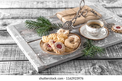 Christmas cookies with coffee and decorations on rustic wooden background