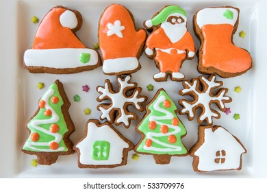 Christmas cookies decorated with colored icing on the white porcelain plate