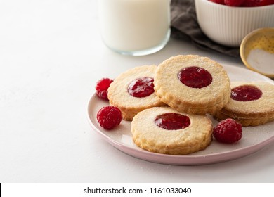 Christmas cookies. Linzer cookies with raspberry jam on white table background. Traditional Austrian biscuits filled. Top view and copy space