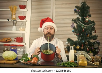 Christmas cookies at man cook in kitchen. Thanksgiving day and Christmas. Family dinner and new year recipe. New year cuisine, menu and food. Chef man in santa claus hat cooking. turkey, pasta, dish.