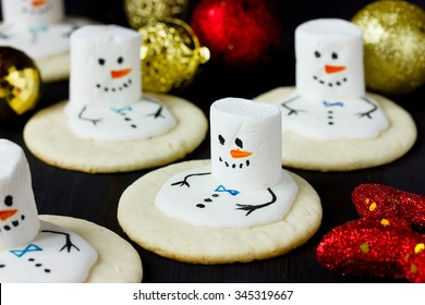 Christmas cookies melting snowman on a black background, focus on one snowman