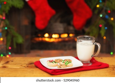 Christmas cookies and milk out for Santa Claus in front of decorated fireplace