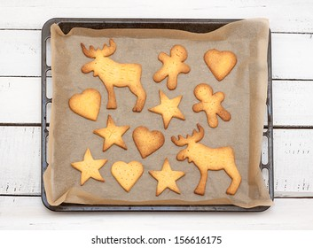 Christmas cookies on a baking tray - white rustic wooden table as background