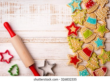 Christmas cookies, rolling pin and cookie cutters on the wooden background.