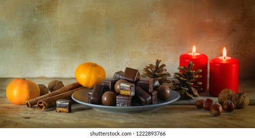 christmas cookies, tangerines, nuts and red candles on a rustic wooden table, panoramic format with copy space, selected focus, narrow depth of field