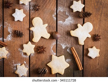 Christmas cookies and tinsel on a dark wooden background. Top view
