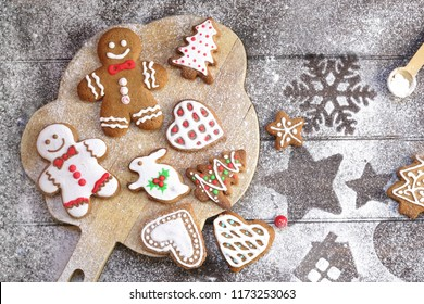 Christmas cookies of various shapes in sugar glaze on a cutting board on a brown wooden table sprinkled with flour, flat lay. Christmas composition with gingerbread men, fir-trees, rabbit