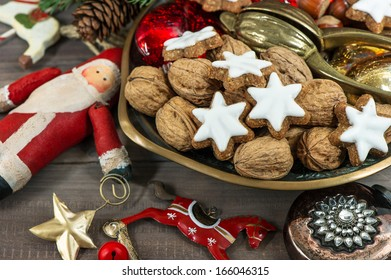 christmas cookies and walnuts with vintage decorations on wooden background