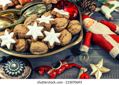 christmas cookies and walnuts with vintage decorations on wooden background. retro style toned picture