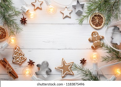 Christmas cookies,fir branch and Christmas lights on wooden table