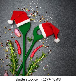 Christmas cooking background with  Kitchen green silicone spoons in Santa Claus red hats, pepper, peperoni, salt, rosemary, on dark background, top view. Herbs and spices Christmas top table.