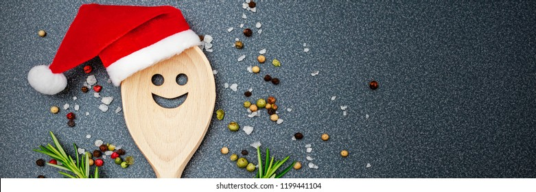 Christmas cooking background with Kitchen wooden spoon with face in red Santa Claus hat, pepper, peperoni, salt, rosemary, garlic , on dark  background, top view. Christmas top table banner