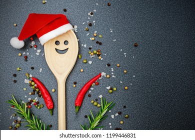 Christmas cooking background with Kitchen wooden spoon with face in red Santa Claus hat, pepper, peperoni, salt, rosemary,  on dark  background, top view. Herbs and spices Christmas top table