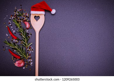 Christmas cooking background with Kitchen wooden spoon with heart in red Santa Claus hat, pepper, peperoni, salt, rosemary, garlic, on dark  background, top view. Herbs and spices Christmas top table