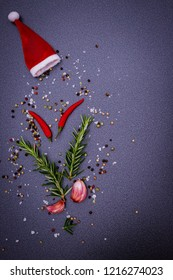 Christmas cooking background with red Santa Claus hat, pepper, peperoni, salt, rosemary, garlic, on dark  background, top view. Herbs and spices Christmas top table