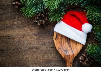 Christmas cooking concept - A wooden spoon with Santa hat and pine cones on dark rustic wooden background. Overhead view with copy space for your text