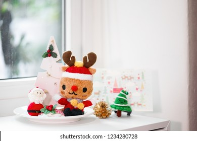 Christmas corner. A Christmas corner decoration by the window with selective focus on the cute reindeer wearing Santa Claus suit plushie. Cute crochet doll of Santa Claus & Christmas tree on the side.