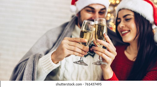 Christmas couple cheers together near ornate festive Eve on Sata Claus hats. Holidays celebrations family  together