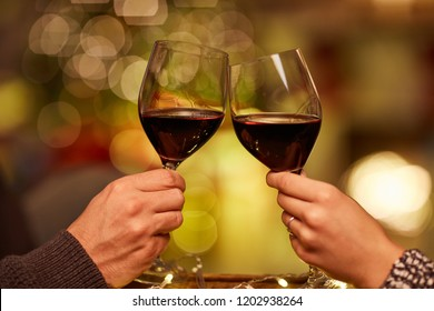 Christmas couple at home in Winter. Couple clinking glasses and drinking red wine at home in Christmas time.