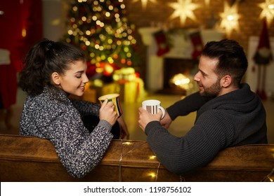 Christmas couple at home in Winter. Happy young couple drinking tea at home in Christmas time. Christmas tree and fireplace in background.