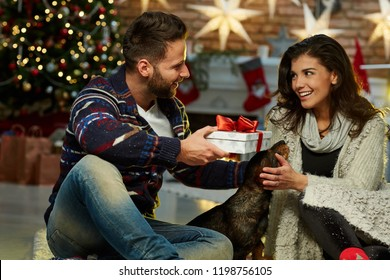 Christmas couple at home in Winter. Happy young couple sitting on floor at home with dog and gift box in Christmas time. Christmas tree and fireplace in background.