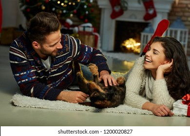 Christmas couple at home in Winter. Happy young couple lying on floor at home with dog Christmas time. Christmas tree and fireplace in background.