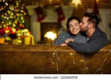 Christmas couple at home in Winter. Happy young couple kissing at home in Christmas time. Christmas tree and fireplace in background.