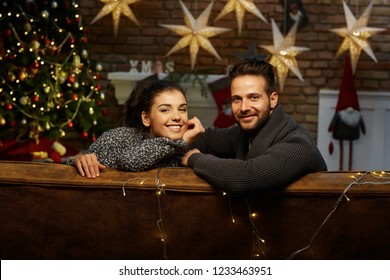Christmas couple at home in Winter. Happy young couple sitting on couch at home in Christmas time. Christmas tree and fireplace in background.