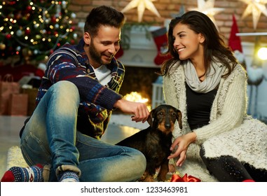 Christmas couple at home in Winter. Happy young couple sitting on floor at home with dog in Christmas time. Christmas tree and fireplace in background.