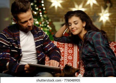 Christmas couple at home in Winter. Happy young couple using tablet computer on sofa at home in Christmas time. Christmas tree in background.