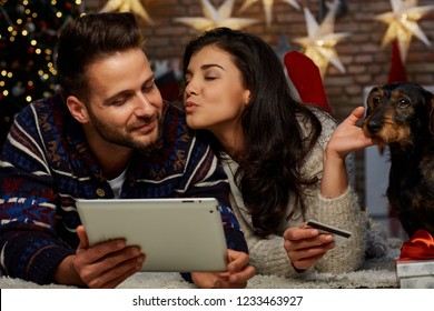 Christmas couple shopping online at home in Winter. Happy young couple lying on floor using tablet and bank card for online shopping at home at Christmas time. Christmas tree and fireplace.