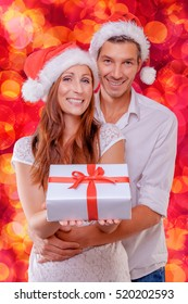 christmas couple smiling with present