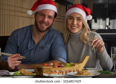 Christmas couple wearing hat eating in a sushi restaurant
