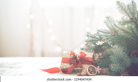 Christmas coziness in a room on a light background, with lights and branches of a Christmas tree and a gift with a red bow on the table, space for text