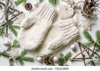 Christmas cozy composition with warm knitted mittens and New Year's accessories and decorations. Preparing for Christmas. View from above. Copy space