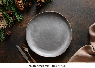 Christmas cozy table setting with empty grey plate and wooden decor on brown table. Rustic home style. Top view, flat lay.