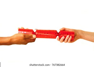 Christmas cracker with hands pulling together on Christmas day on white background stock photo
