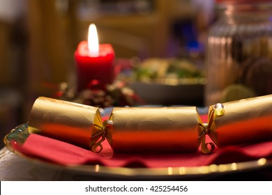 Christmas cracker on a plate with a candle on the background