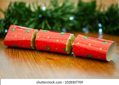 Christmas cracker on a wooden table, with garland in background and fairy lights.