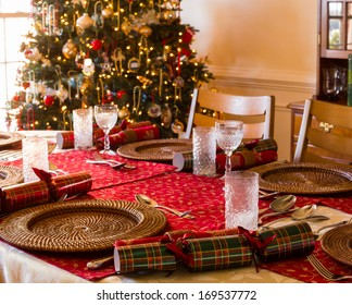 Christmas crackers on table set for Christmas lunch with crackers and decorated tree in background