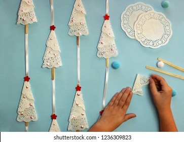 Christmas crafted garland with trees from paper serviettes lays on the blue color background, original craft and diy concept for kid and kindergarten